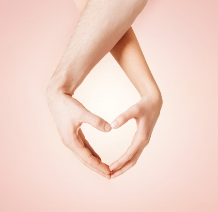 close up of woman and man hands showing heart shape Stock Photo