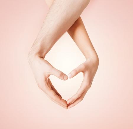 casamento: Feche acima da mulher e do homem mãos mostrando formato de coração