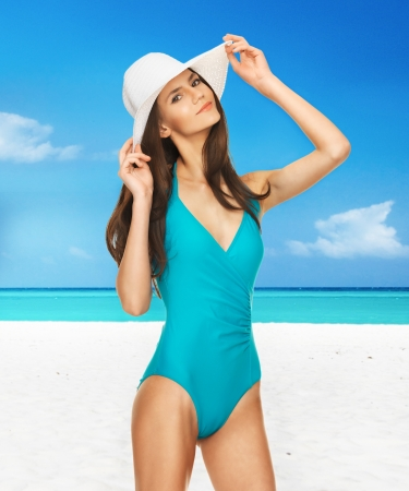 perfect fit: picture of model posing in swimsuit with hat on the beach Stock Photo