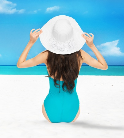 picture of model posing in swimsuit with hat on the beach Stock Photo