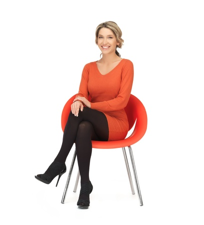 sitting on: nice woman in dress sitting in chair Stock Photo
