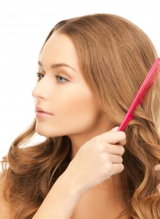 champu: mujer hermosa con el pelo largo y rizado y un cepillo Foto de archivo