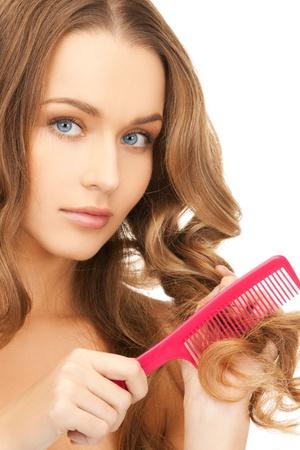 mujer hermosa con el pelo largo y rizado y un cepillo Foto de archivo