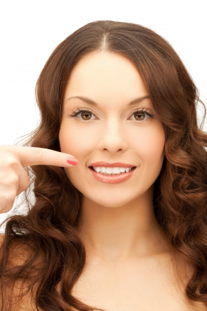 dental calculus: portrait of woman pointing at her toothy smile   Stock Photo