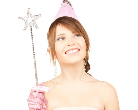 conjuring: happy girl in party cap with magic stick Stock Photo