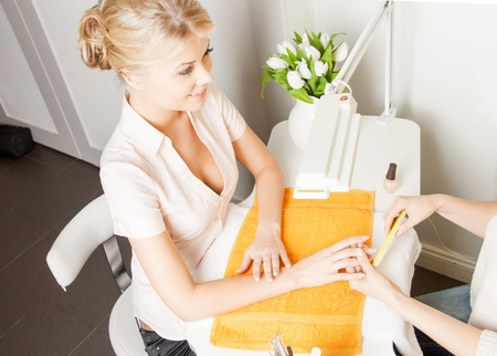 parlor: beautiful woman having a manicure at the salon