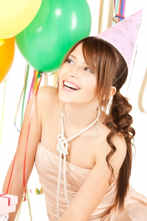 happy girl with colorful balloons in party cap photo