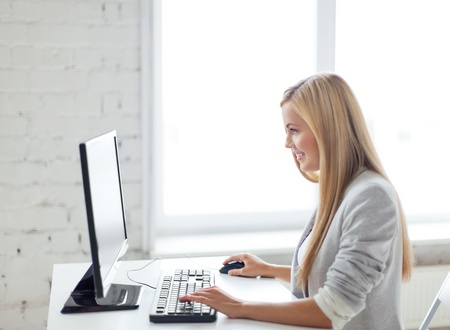 computer learning: picture of smiling businesswoman with computer in office