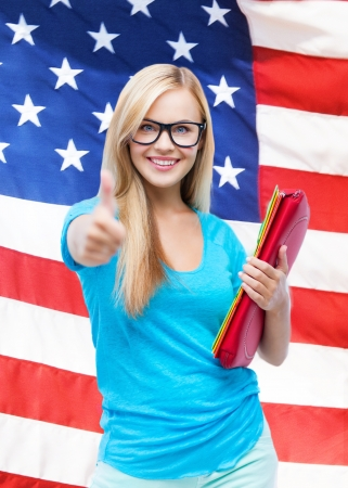 student with folders showing thumbs up over american flag photo