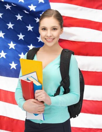 tarjeta visa: sonriente estudiante con libros y schoolbag sobre la bandera americana