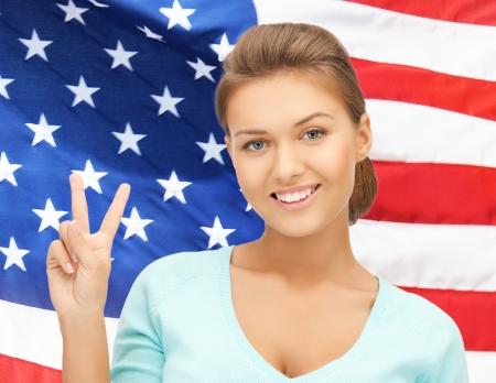 donna che mostra il segno di vittoria o di pace sopra la bandiera americana