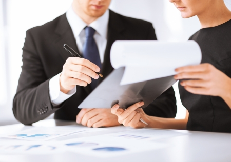 business meetings: picture of businessman and businesswoman signing paper Stock Photo