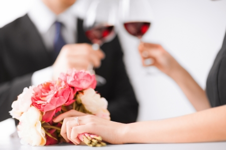 diamond jewellery: picture of engaged couple with wine glasses in restaurant Stock Photo