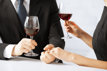 proposing a toast: picture of engaged couple with wine glasses in restaurant Stock Photo