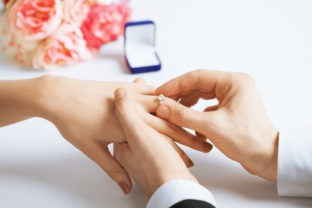 proposals: picture of man putting  wedding ring on woman hand Stock Photo