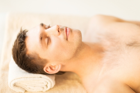 therapeutic massage: close up of man face in spa salon
