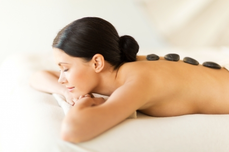 hot stone massage: picture of woman in spa salon with hot stones