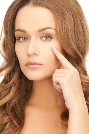 face of beautiful woman pointing at her eye area photo