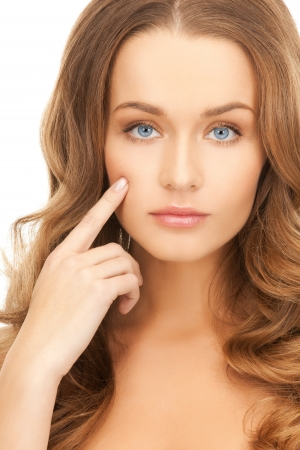 face of beautiful woman pointing at her cheek photo