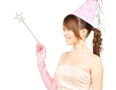wand: happy girl in party cap with magic stick Stock Photo
