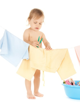 bright picture of adorable baby doing laundry   photo