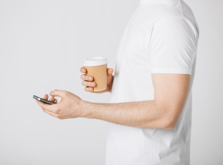 man with smartphone and take away coffee cup photo