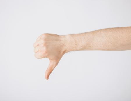 Nahaufnahme von Menschen Hand zeigt Daumen nach unten