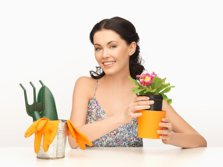 lovely housewife with flower in pot and gardening set photo