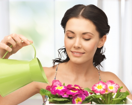 lovely housewife with flower in pot and watering can photo