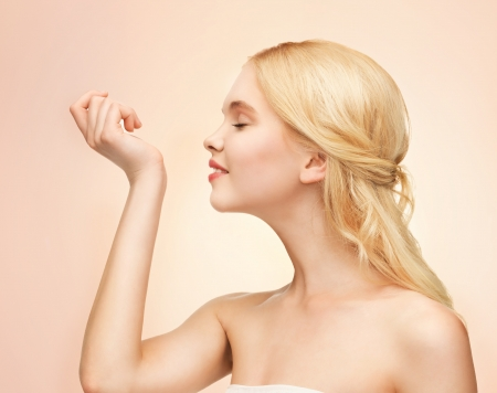 picture of young girl smelling perfume on her hand photo