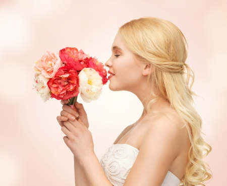 picture of young woman smelling bouquet of flowers photo