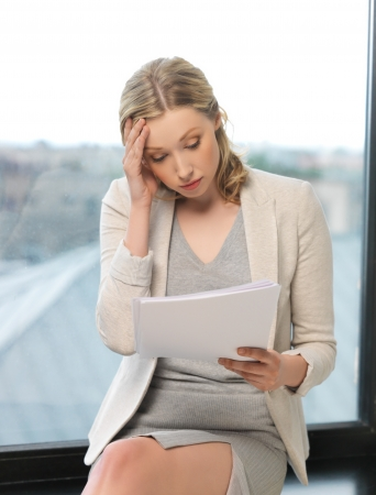 indoor picture of bored and tired woman with documents photo
