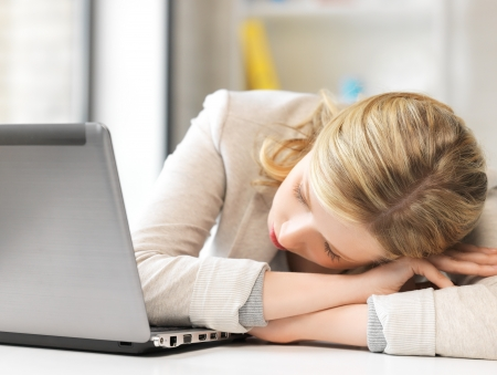 indoor picture of bored and tired woman sleeping on the table Stock Photo - 20021205