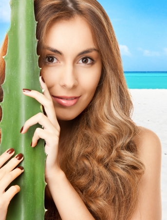 anti season: lovely woman with aloe vera over tropical beach background Stock Photo