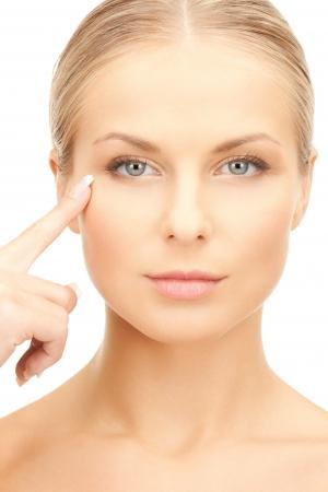 tratamiento facial: frente a la hermosa mujer que señala en su área de los ojos