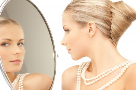 真珠と鏡を見てからネックレスを持つ女性