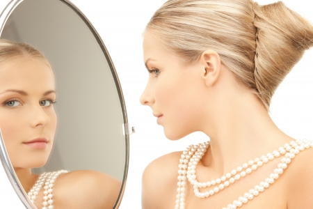 mirror face: woman with necklace from pearls and looking into the mirror