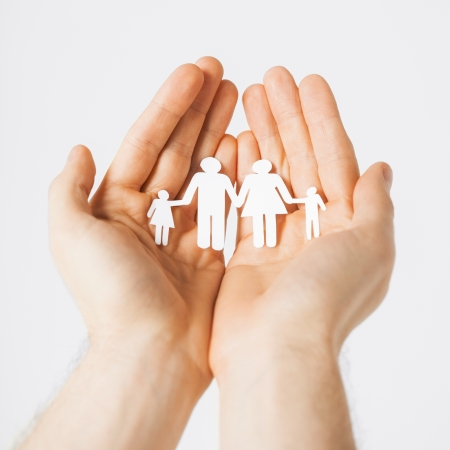 protection concept: man hands showing family of paper men