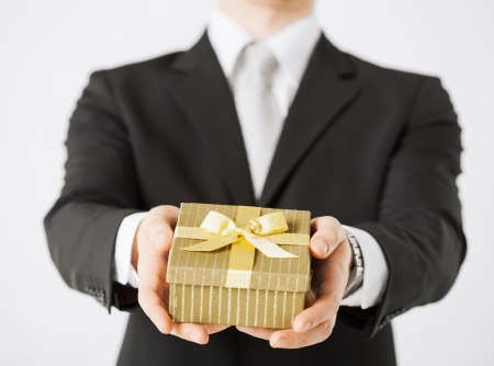 birthday suit: close up of man hands holding gift box  Stock Photo