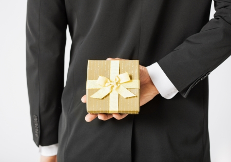 people from behind: close up of man hands holding gift box Stock Photo