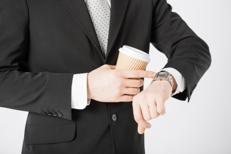 rushing hour: close up of man with take away coffee looking at wristwatch