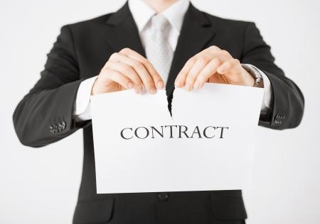 beeld van de man handen scheuren contract papier