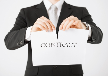 dismissal: picture of man hands tearing contract paper