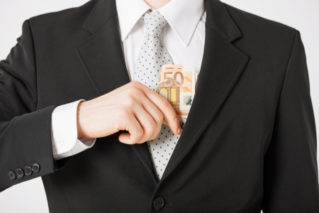 putting money in pocket: man hand putting euro cash money into suit pocket Stock Photo