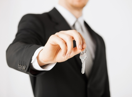 bright picture of man hand holding house keys photo