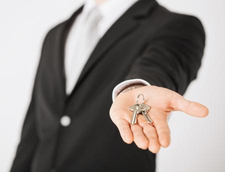 agente comercial: brillante imagen de hombre de mano que sostiene las llaves de casa