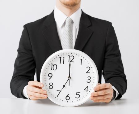 seven o'clock: close up of man holding wall clock