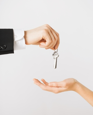 Realtor: picture of man hand passing house keys to woman Stock Photo