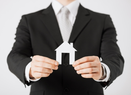 agente comercial: foto de las manos del hombre que sostienen la casa de papel