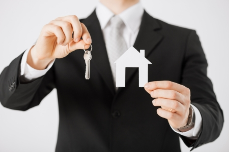 man hand holding house keys and paper house Stock Photo - 20075048
